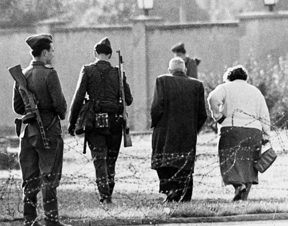 Вдоль стены располагались 302 вышки с часовыми и стрелками-снайперами, к охране были привлечены свыше 10 тыс. военнослужащих ГДР. На фото: пара возвращается в Восточный Берлин после отказа в пересечении границы, 1961 год