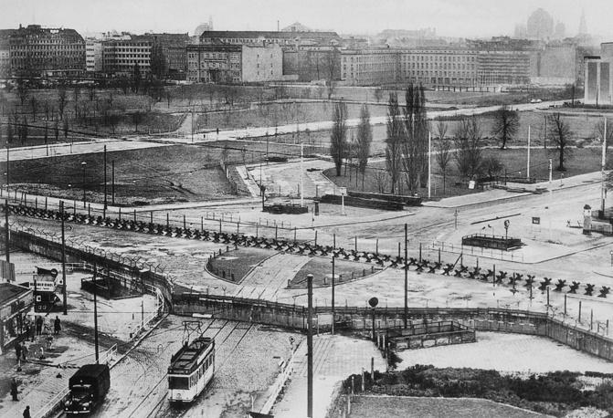 Стена была собрана из 45 тыс. бетонных блоков, закругленных сверху, и на всем протяжении была обтянута колючей проволокой. На фото: Берлинская стена, 1962 год