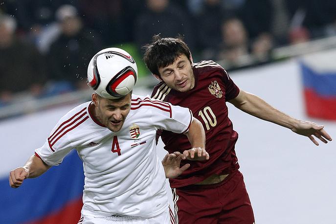Игроки сборных России и Венгрии Алан Дзагоев и Тамаш Кадар в борьбе за мяч