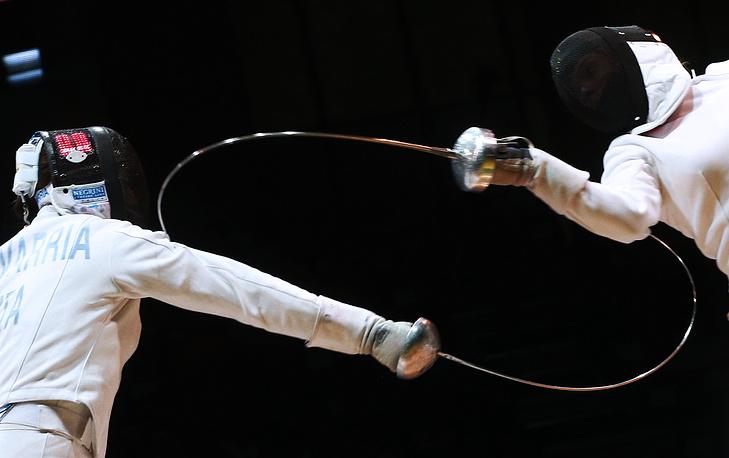 23 июля. Итальянская спортсменка Мара Наваррия и венгерская спортсменка Хайналка Тот в поединке за третье место на соревнованиях командного первенства по фехтованию на шпагах среди женщин на чемпионате мира 2014 года в Казани. Российские шпажистки стали победителями командного турнира