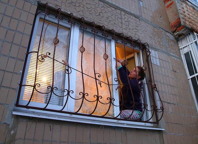 Сильно разрушенные дома восстанавливать пока не планируют. Но если дом пострадал незначительно, его оперативно ремонтируют. На фото: жительница квартиры одного из домов в районе Текстильщик заклеивает разбитое в результате обстрела окно