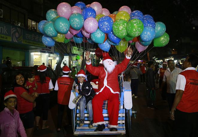 Мужчина в костюме Санта-Клауса на рождественском карнавале в Мумбае, Индия, 23 декабря