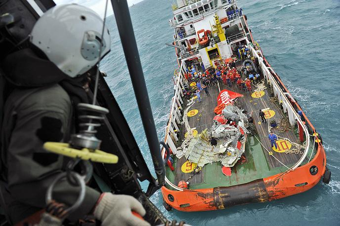 """Спасатели подняли со дна Яванского моря хвостовую часть самолета AirAsia. Специалисты не обнаружили """"черных ящиков"""" в найденных обломках. Работы по поиску фюзеляжа  разбившегося самолета продолжатся в воскресенье. На фото: поднятие хвостовой части самолета авиакомпании AirAsia, 10 января"""