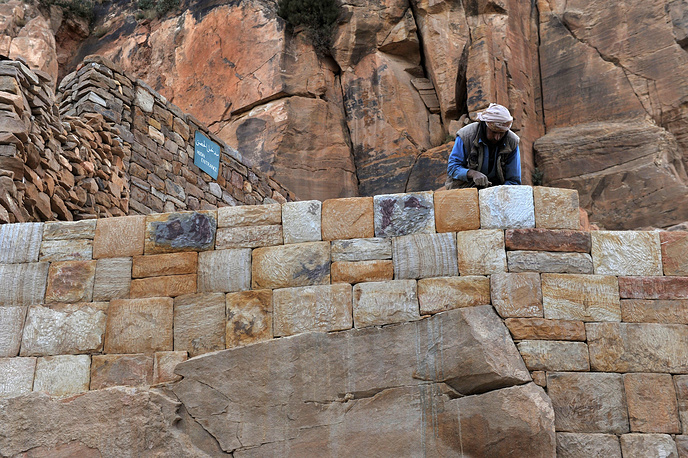 Рабочий ремонтирует каменную стену в старом городе Суля