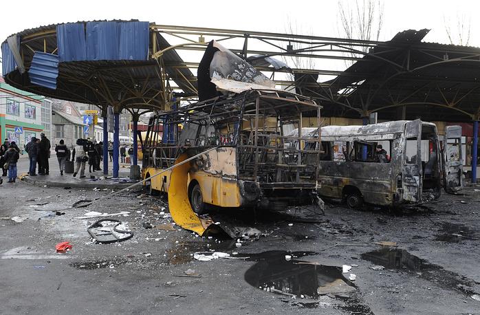 11 февраля в результате попадания снаряда в автобусную станцию в центре Донецка шесть человек погибли, еще восемь получили ранения. На фото: сгоревшие маршрутка и рейсовый автобус на автостанции в Донецке, 11 февраля