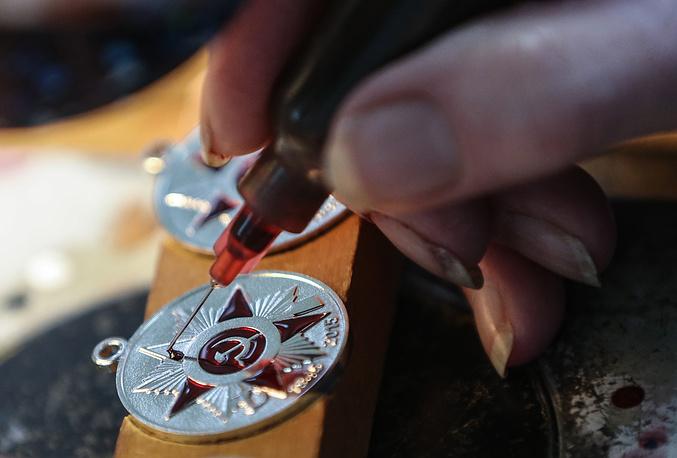 Нанесение эмали происходит с помощью специального шприца. На фото: прокладка ювелирной эмали в рельеф медали