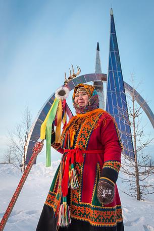 """Участники выездной сессии постоянного форума ООН по вопросам коренных народов во время совместного фотографирования с местной фольклорной группой у стелы """"66 параллель"""""""