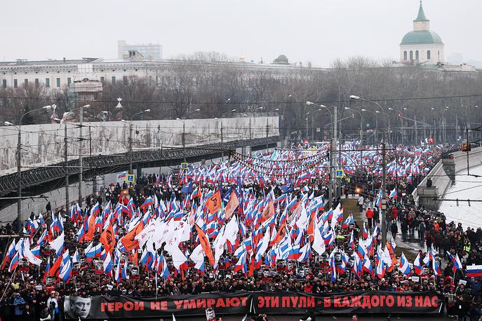 """Манифестанты несли российские флаги с траурными лентами, портреты Немцова, плакаты с лозунгом """"Герои не умирают и эти пули - в каждого из нас"""". Этот же лозунг был написан на транспаранте, который несли во главе траурной колонны"""
