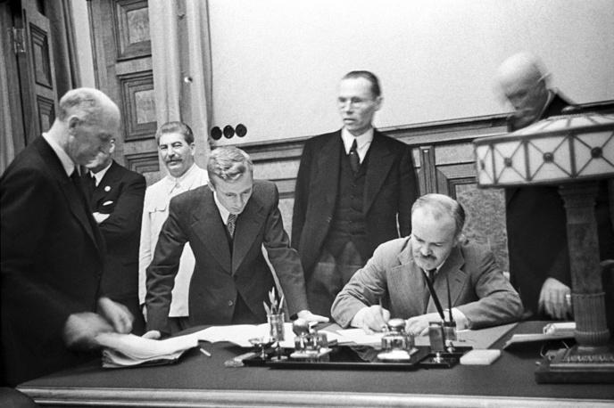 В 1939 году Молотов был назначен наркомом иностранных дел. Одним из самых известных и неоднозначных по оценке его действий на этом посту было подписание советско-германского пакта о ненападении. На фото: Молотов подписывает советско-германский договор. На церемонии присутствует Сталин. Август 1939 года