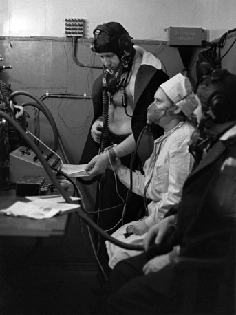 Алексей Леонов и Павел Попович под наблюдением лаборанта (в кислородной маске) проходят обследование в барокамере, где созданы усовия, соответствующие высоте 5000 метров, 1968 год