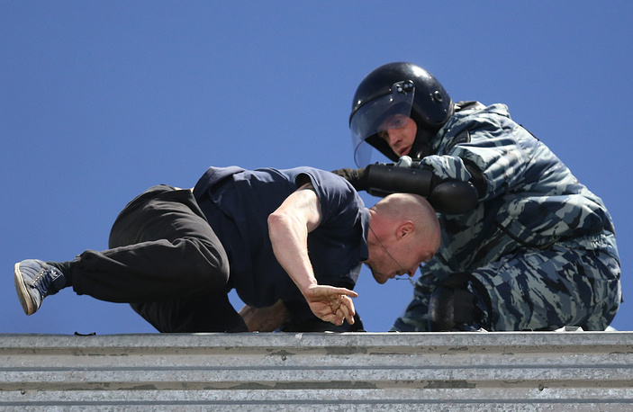 Боец ОМОНа и болельщик на крыше стадиона во время матча