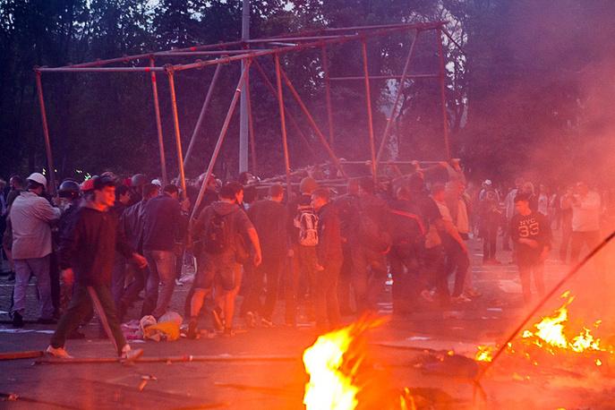 Местные жители несут металлическую конструкцию для эвакуации людей, заблокированных в горящем здании Дома профсоюзов, Одесса, 2 мая 2014 года