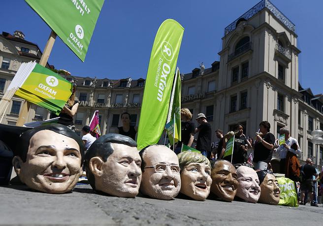 """Демонстрация проходит под девизом """"Остановить TTIP (Трансатлантическое соглашение о партнерстве в области торговли и инвестиций между ЕС и США) - спасти климат - бороться с бедностью"""".  На фото: маски с лицами премьер-министра Италии Маттео Ренци, премьер-министра Канады Стивена Харпера, президента Франции Франсуа Олланда, канцлера Германии Ангелы Меркель, президента США Барака Обамы, премьер-министра Великобритании Дэвида Кэмерона и премьер-министра Японии Синдзо Абэ (слева направо)"""