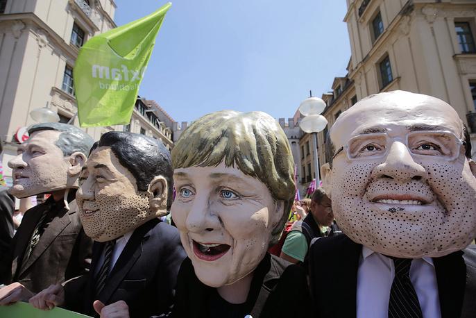 На фото: демонстранты в масках государственных лидеров, принимающих участие в саммите G7