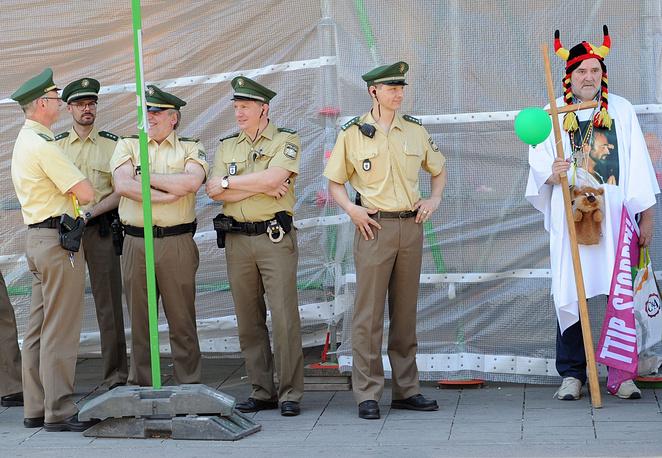 В правоохранительных органах отметили, что инцидентов пока не зафиксировано.  На фото: полицейские стоят рядом с активистом, выступающим против проведения саммита G7