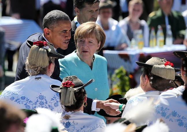 Перед началом саммита канцлер Германии Ангела Меркель провела встречу с президентом США Бараком Обамой в коммуне Крюн. Местные жители организовали для первых лиц торжественный прием с баварским колоритом - звуками альпийских рожков, пивом и кренделями. На фото: Барак Обама и Ангела Меркель приветствуют жителей коммуны Крюн