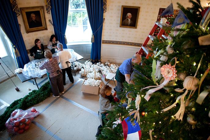 Волонтеры и сотрудники Белого дома украшают елку в Голубой комнате, 30 ноября 2010 года
