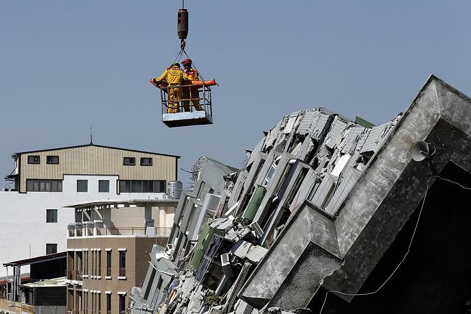 Спасатели извлекают выжившего из разрушенного в результате землетрясения здания. Подземный толчок магнитудой 6,4 привел к разрушению десятка строений на юго-западе острова, Тайвань, 8 февраля