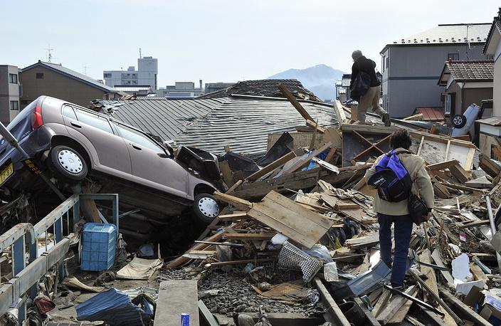 Пожилая пара перелезает через мусор, чтобы добраться до своего дома в разрушенном цунами районе Кесеннумы, префектура Мияги, северная Япония, 14 марта 2011 года