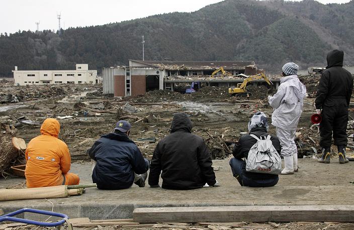 Родственники детей и учителей начальной школы Окава наблюдают за ходом поисковых работ в Исиномаки, префектура Мияги, примерно в 350 км к северу от Токио, 22 марта 2011 года