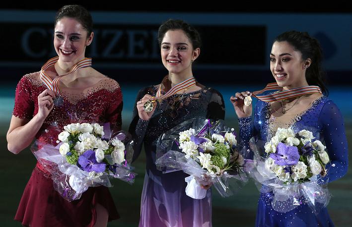 Канадская спортсменка Кейтлин Осмонд, завоевавшая серебряную медаль, Евгения Медведева, завоевавшая золотую медаль, и канадская спортсменка Габриэль Дэйлман (слева направо), завоевавшая бронзовую медаль, во время церемонии награждения