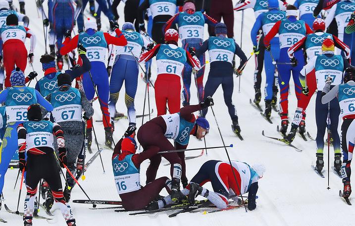 Олимпийские спортсмены из России Денис Спицов и Андрей Ларьков, а также Симен Хегстад Крюгер из Норвегии во время лыжных гонок