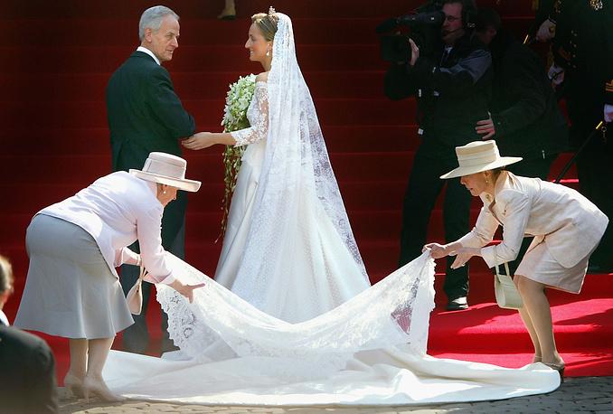 Клэр Бельгийская (Клэр Луиз Кумбс), супруга принца Лорана, младшего брата ныне правящего короля Филиппа, в сопровождении своего отца Карла Кумбса на ступеньках собора Сен-Мишель-э-Гюдюль в Брюсселе, 12 апреля 2003 года