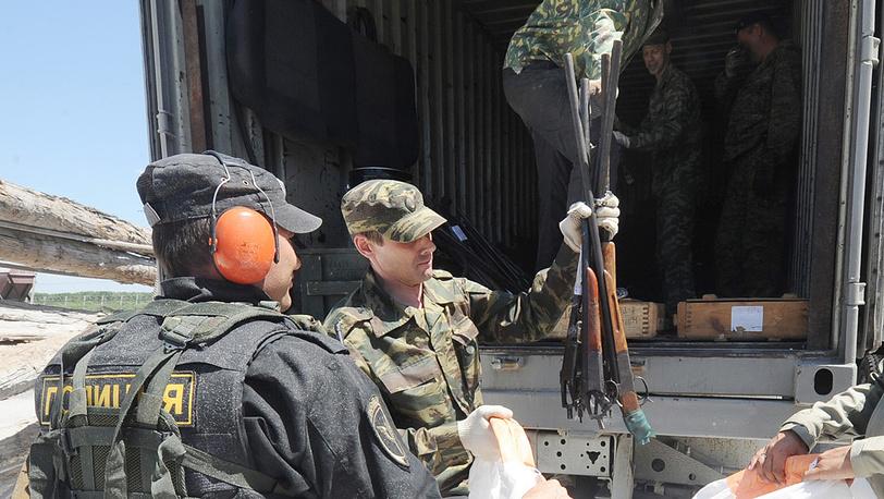 Сотрудники правоохранительных органов выгружают изъятое оружие
