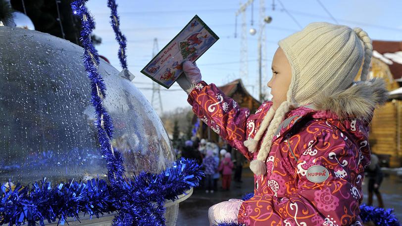Ребенок опускает в почтовый ящик письмо для Деда Мороза