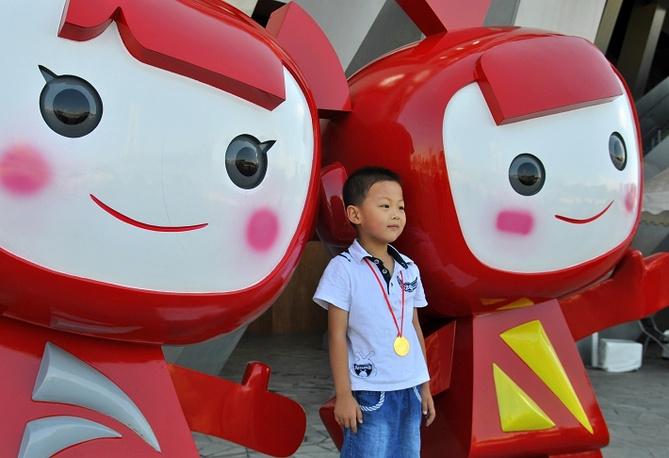 Жители и гости Пекина охотно фотографируются с олимпийскими талисманами на фоне объектов