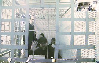 Фигурант по делу об убийстве политика Бориса Немцова Хамзат Бахаев (на экране в центре) во время рассмотрения жалобы на его арест в Мосгорсуде