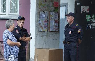 Сотрудники правоохранительных органов у подъезда жилого дома, где проживал обвиняемый с семьей