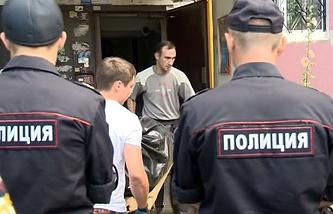 Сотрудники правоохранительных органов у подъезда жилого дома, где проживал Олег Белов с семьей