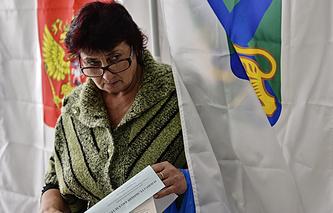 Жительница села Вольно-Надеждинское во время голосования на избирательном участке №1817 на выборах главы Надеждинского сельского поселения