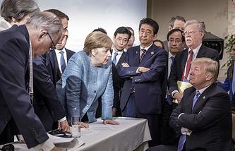 Президент Франции Эмманюэль Макрон (третий слева), канцлер Германии Ангела Меркель, премьер-министр Японии Синдзо Абэ, помощник президента США по нацбезопасности Джон Болтон и президент США Дональд Трамп