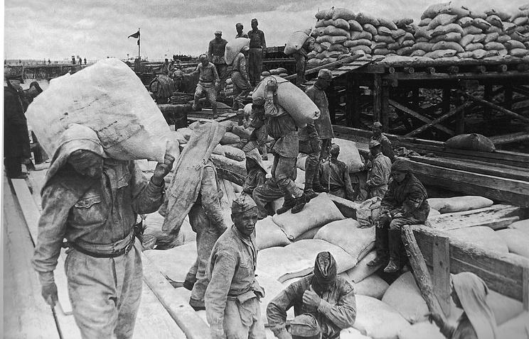Советские солдаты разгружают баржу с мукой в ладожском порту Осиновец предназначенную  для  блокадного Ленинграда. Лето 1942 г.