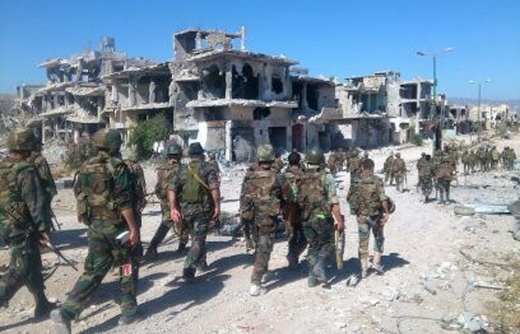 Солдаты сирийской армии патрулирует город Кусейр недалеко от ливанской границы в провинции Хомс, Сирия. 5 июня 2013 года