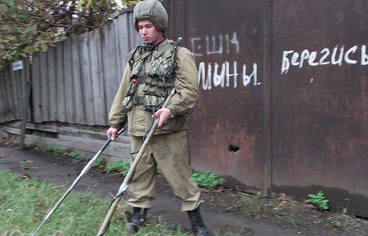 Сапер проводит инженерную разведку для выявления заложенных фугасов на одной из улиц Грозного