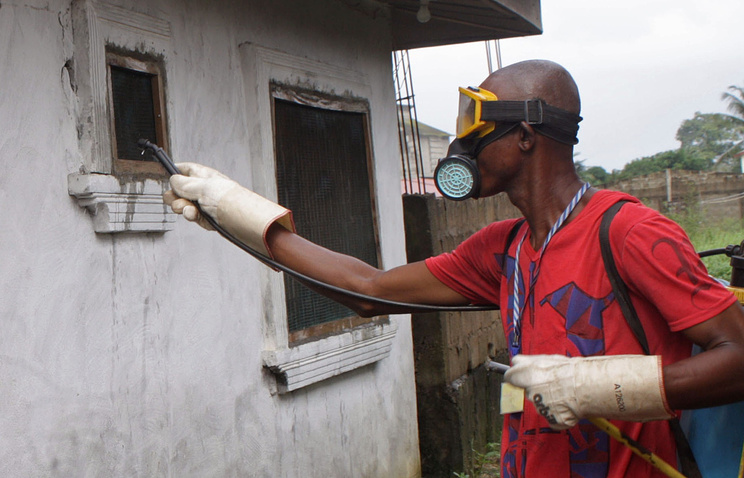 Мужчина распыляет специальный спрей для предотвращения распространения вируса Эболы