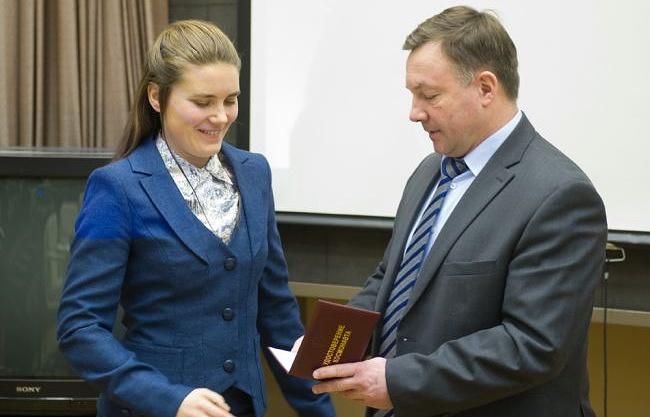 Начальник ЦПК Юрий Лончаков вручает удостоверение космонавта-испытателя Анне Кикиной