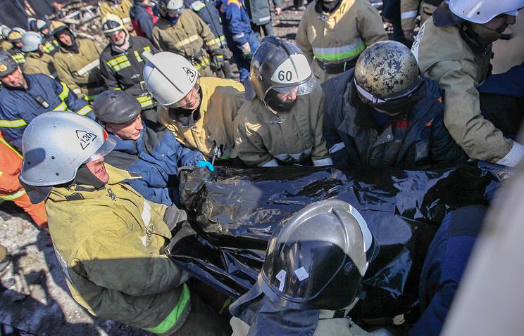 """Спасатели с телом человека, извлеченным из-под завалов после пожара в торговом центре """"Адмирал"""""""