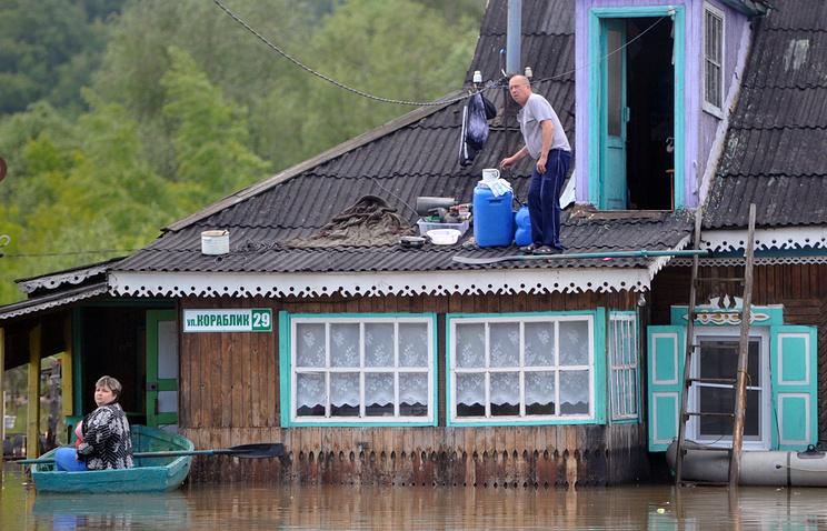 Местные жители в подтопленном поселке Ильича в Барнауле, Алтайский край. Июнь 2014 года
