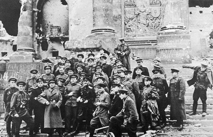 Военные фотокорреспонденты, кинооператоры, писатели и журналисты у стен поверженного Рейхстага. 5 мая 1945 года