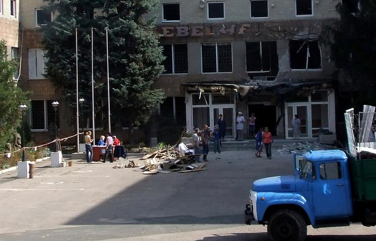 Жители Донецка во время уборки территории Краеведческого музея, частично разрушенного в результате артиллерийского обстрела