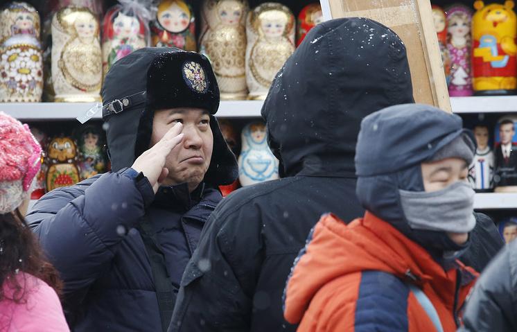 Турист из Китая в сувенирном магазине на Манежной площади